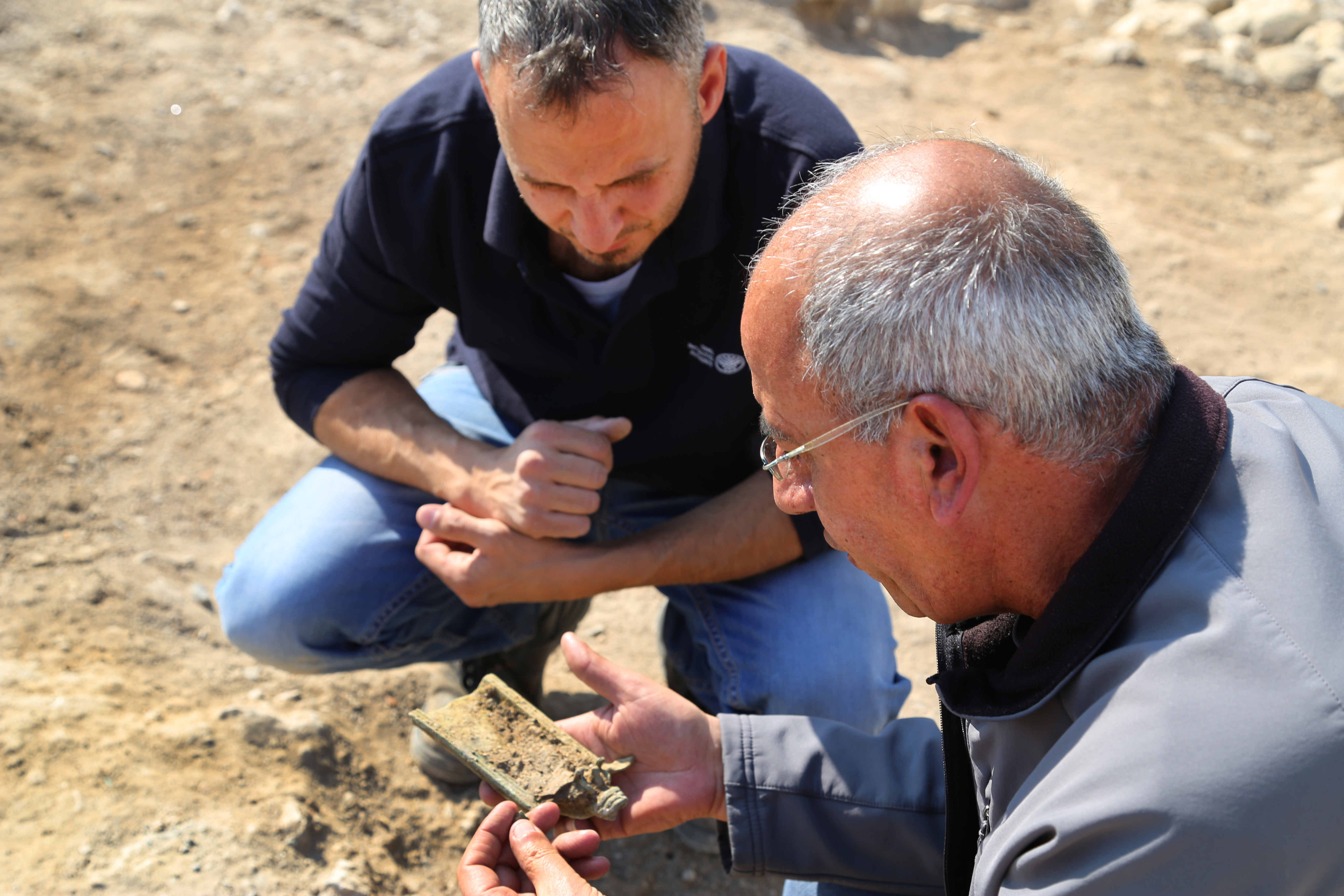 Eyad Bisharat views the bronze incense shovel being held by Arfan Najar, at Magdala where it was discovered. Photo: Israel Antiquities Authority