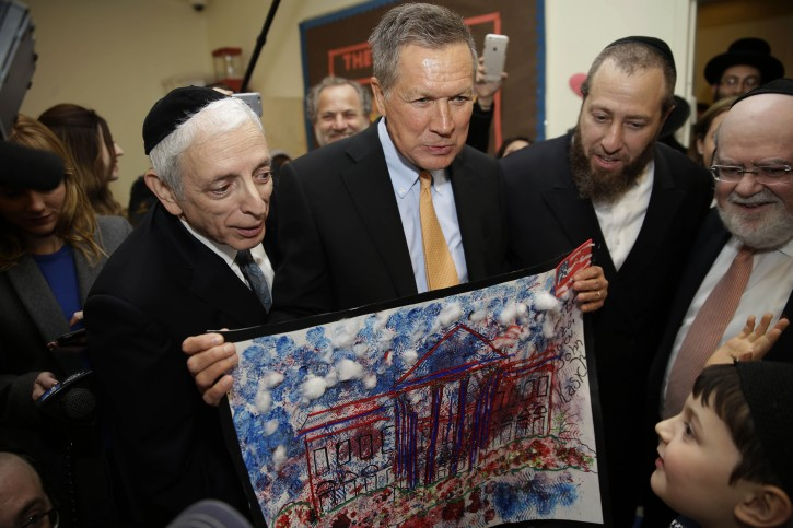 Republican presidential candidate,,Ohio Gov. John Kasich looks at a picture of the White House made by students at 'Shema Kolainu-Hear Our Voices' school a center for children with autism in the Brooklyn borough of New York, Tuesday, April 12, 2016. (AP Photo/Seth Wenig)