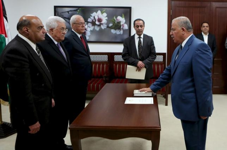 Adnan Abu Laila, a member of the Palestinian constitutional court, is sworn in by President Mahmoud Abbas (2nd L) in the West Bank city of Ramallah April 11, 2016. REUTERS
