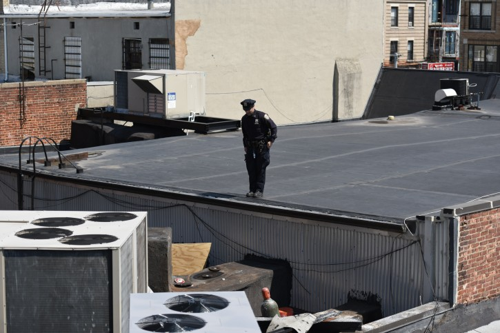 A Police officer stands guard on the rooftop above HSBC bank on 13th Ave where a thief dug a hole and made off with nearly 300K worth of valuables. (Eli Wohl/VINnews.com)