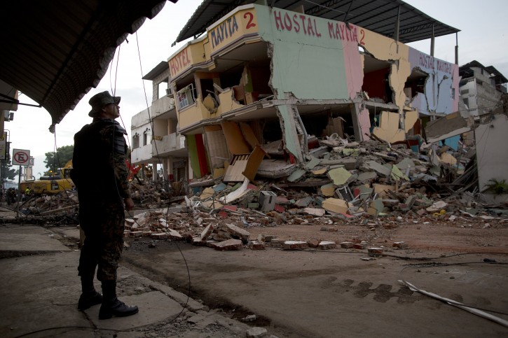 An air force soldier stands guard in front of buildings collapsed by an earthquake in Manta, Ecuador, Monday, April 18, 2016. A Saturday night quake left a trail of ruin along Ecuador's Pacific Ocean coast. Hundreds died and thousands are homeless. (AP Photo/Rodrigo Abd)