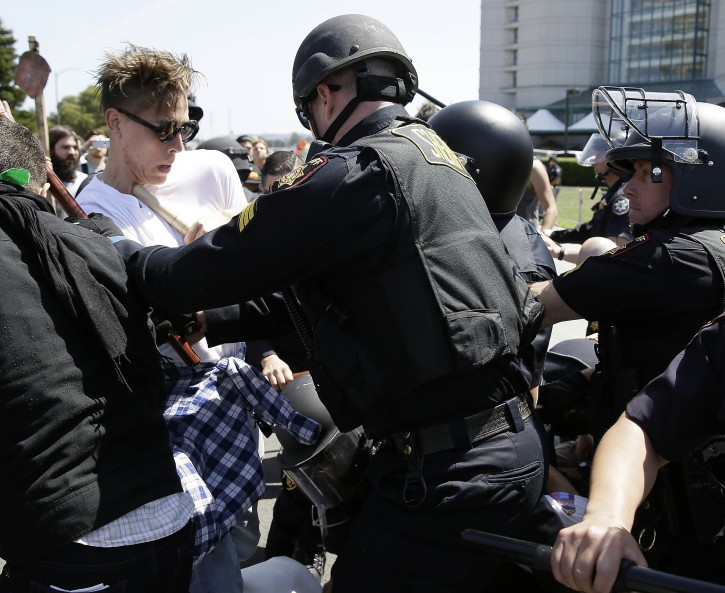 Police officers push back a group protesting Republican presidential candidate Donald Trump outside of the Hyatt Regency hotel during the California Republican Party 2016 convention in Burlingame, Calif., Friday, April 29, 2016. (AP Photo/Eric Risberg)