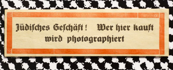 A sticker from around 1938 reading: 'Jewish shop! Whoever buys here will be photographed' is displayed at an exhibition of antisemitic and racist stickers at the Deutsches Historisches Museum, German Historic Museum, in Berlin, Tuesday, April 19, 2016. One of Germany's main history museums is exhibiting racist and anti-Semitic stickers spanning more than a century, a show that comes as the country worries about racism amid the migrant crisis. (AP Photo/Markus Schreiber)