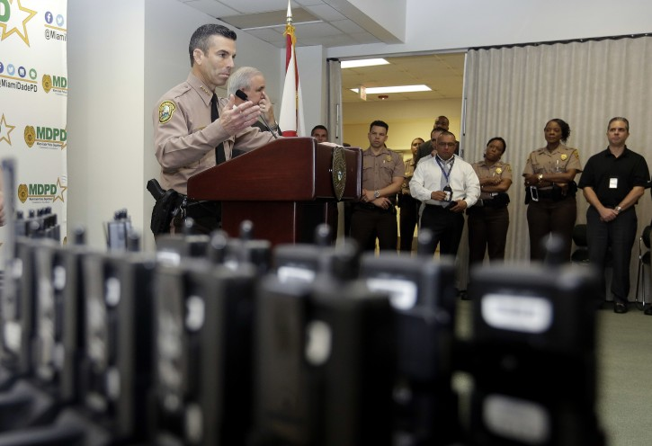 Miami-Dade Police Department Director Juan Perez talks about the department's plan to outfit 1,000 of its officers with body cameras, shown in the foreground, during a news conference, Thursday, April 28, 2016, in Doral, Fla. Police body cameras have become more popular following a number of controversial officer shootings around the country. (AP Photo/Lynne Sladky)