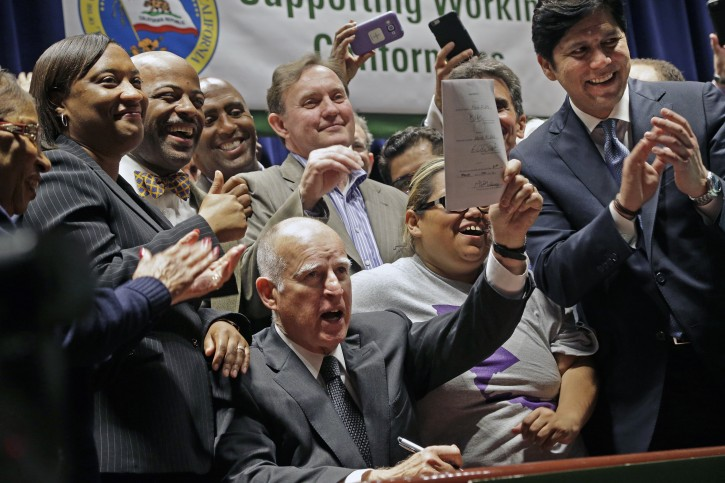 California Gov. Jerry Brown lifts a signed bill creating highest statewide minimum wage at $15 an hour by 2022 at the Ronald Reagan building in Los Angeles, Monday, April 4, 2016. (AP Photo/Nick Ut)