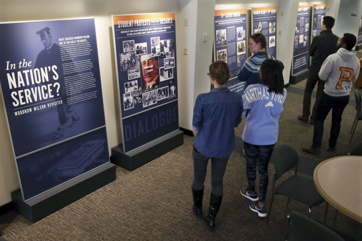 "Princeton University students walk through an exhibit titled, ""In the Nation's Service? Woodrow Wilson Revisited,"" Sunday, April 3, 2016, at the Woodrow Wilson School of Public and International Affairs in Princeton, N.J. As Princeton University officials weigh whether to remove alumnus and former President Woodrow Wilson's name from its public policy school, the college is launching an exhibit meant to more fully air his legacy. The Nobel Peace Prize winner heralded as a progressive hero has also faced criticism as a racist who encouraged segregation in his administration. (AP Photo/Mel Evans)"