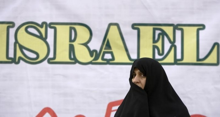 FILE - A woman stands next to an anti-Israel banner during a demonstration to mark the anniversary of the seizure of the U.S. embassy in Tehran November 4, 2007.  Reuters