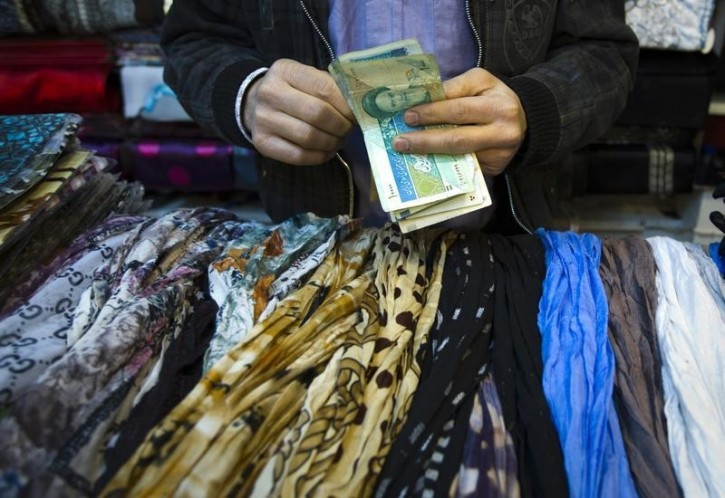 FILE - A shopkeeper counts Iranian bank notes at his shop in a bazar in Tehran February 25, 2012. REUTERS/Raheb Homavandi