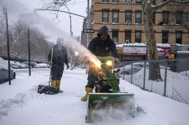 FILE - A man plows a sidewalk after a snow storm in the Brooklyn borough of New York January 27, 2015.  Reuters