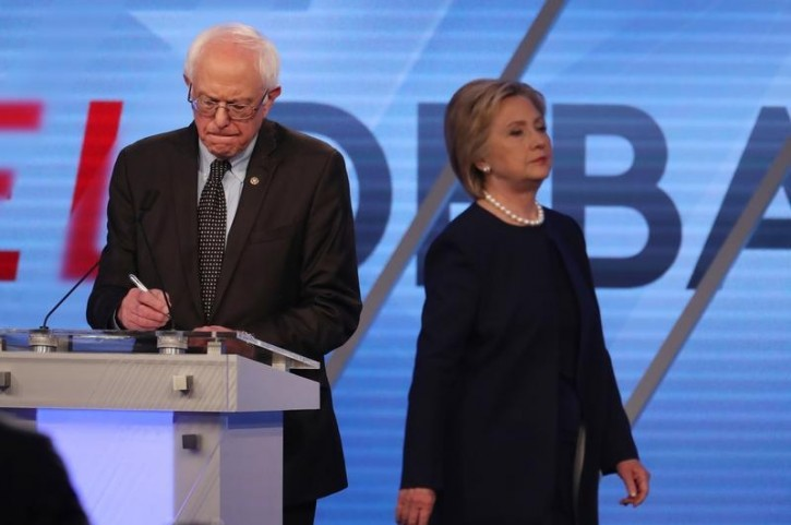 FILE - Democratic U.S. presidential candidate Senator Bernie Sanders writes on his notes as his rival Hillary Clinton walks behind him during a commercial break at the Univision News and Washington Post Democratic U.S. presidential candidates debate in Kendall, Florida March 9, 2016.   REUTERS/Carlo Allegri