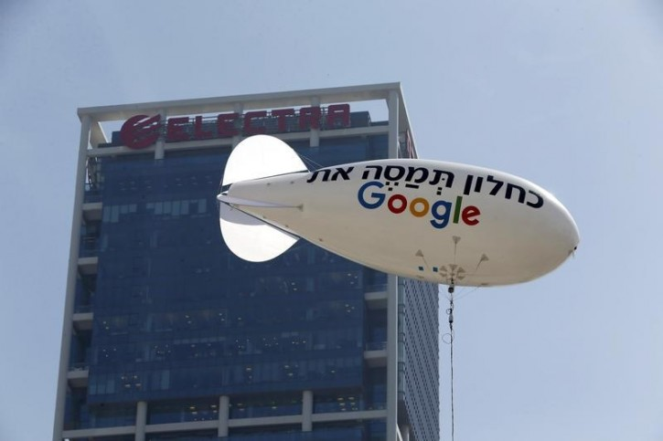 """A blimp reading """"Kahlon, tax Google"""", in reference to Finance Minister Moshe Kahlon, is seen floating near the building hosting Google's offices in Tel Aviv in this April 3, 2016 file photo.  The other side of the blimp bears the English slogan """"Google must pay tax"""".  REUTERS/Baz Ratner/Files"""