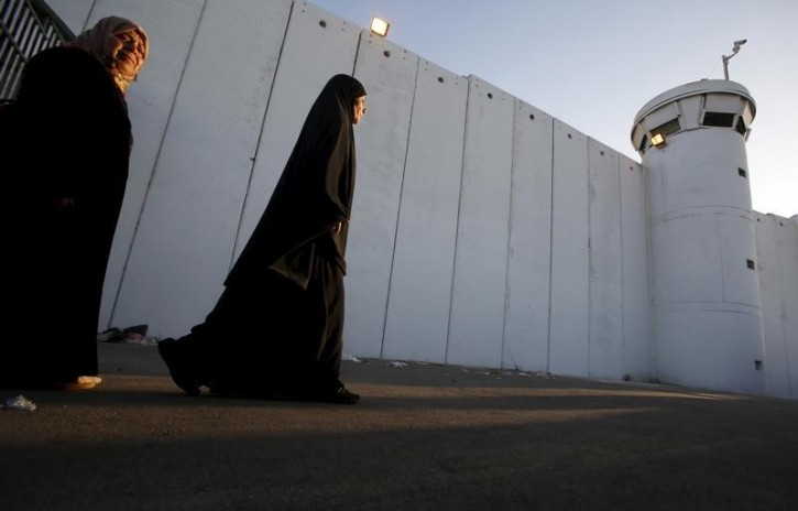 FILE - Palestinian women make their way to attend the third Friday prayer of Ramadan in Jerusalem's al-Aqsa mosque, through an Israeli checkpoint in the West bank city of Bethlehem, July 3, 2015. REUTERS/Mussa Qawasma