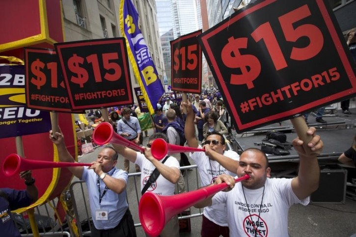 FILE - People celebrate the passage of the minimum wage for fast-food workers by the New York State Fast Food Wage Board during a rally in New York July 22, 2015.  Reuters