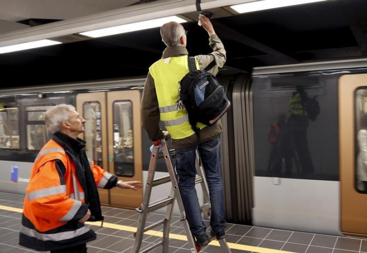 Workers clean a security camera on a platform after Maelbeek metro station reopened on Monday in Brussels, Belgium, April 25, 2016.    REUTERS/Francois