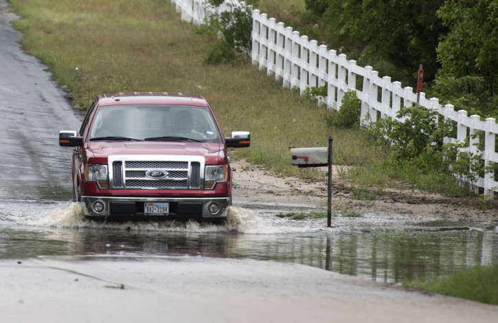 A man drives through floodwaters near the Ozarka Wood County Bottling Plant in Hawkins, Texas, Saturday, April 30, 2016.  AP