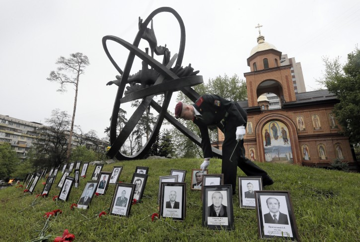 A soldier places portrait photos near the monument erected in memory of the victims of the Chernobyl explosion in Ukraine's capital Kiev, Ukraine, Tuesday, April 26, 2016. Ukraine marks the 30th anniversary of the Chernobyl nuclear disaster, which spread radiation over much of northern Europe. (AP Photo/Efrem Lukatsky)