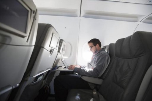FILE - A man uses his laptop  while on a special JetBlue media flight out of John F. Kennedy International Airport in New York December 11, 2013.   REUTERS/Lucas Jackson