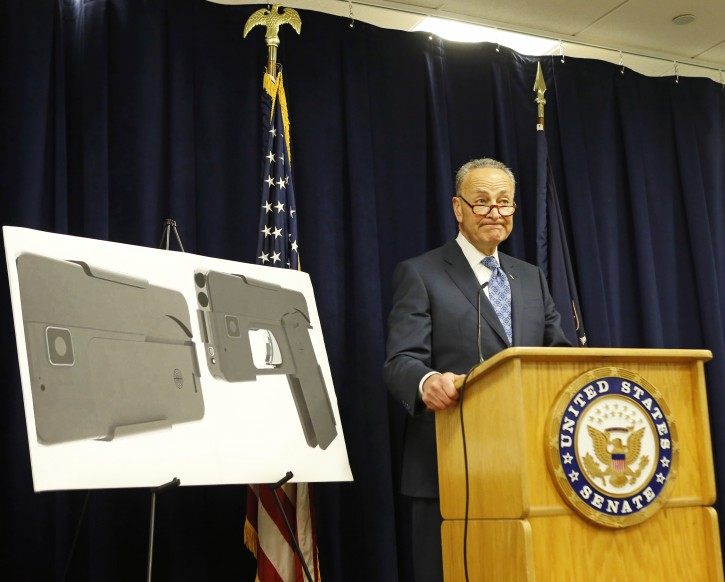 U.S. Sen Charles Schumer, (D-New York), stands beside two photographs of what appears to be a cell phone, but is actually a handgun, during a press conference in his office, Monday, April 4, 2016, in New York. According to the website of Ideal Conceal, the company that is developing the product, their handgun is a double-barreled .380 caliber gun that can serve as a concealed weapon. (AP Photo/Kathy Willens)