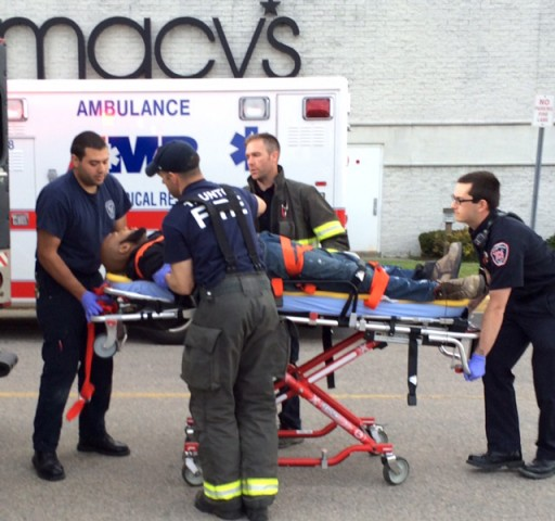 The suspect in attacks at Silver City Galleria mall is transported on a gurney into an ambulance by medical personnel in Taunton, Mass., Tuesday, May 10, 2016. Multiple people have been stabbed in separate deadly attacks at the mall and a home in Massachusetts. Authorities say an off-duty law enforcement officer shot and killed the suspect. (Charles Winokoor/The Daily Gazette via AP)