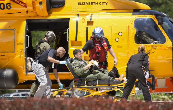 A Navy aviator involved in a crash is brought into Sentara Norfolk General Hospital's emergency department after exiting a coast guard helicopter under his own power in Norfolk, Va., Thursday, May 26, 2016. Two Navy jet fighters collided off the coast of North Carolina during a routine training mission on Thursday, sending several people to the hospital, officials said. (L. Todd Spencer/The Virginian-Pilot via AP)