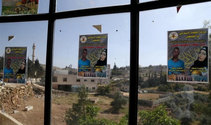 FILE - Posters of Palestinian Maram Abu Ismail, 23, and her 16-year-old brother, Ibrahim Taha, who the Israeli police said were shot dead by the police after they tried to carry out an attack with knives at a checkpoint, are seen on a window at a mourning house near the West Bank city of Ramallah, April 27, 2016. REUTERS/Mohamad Torokman