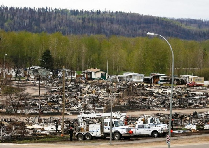 Crews begin to work on the burned out remains of the Waterways neighbourhood of Fort McMurray, Alberta, Canada, May 9, 2016 after wildfires forced the evacuation of the town. REUTERS/Chris Wattie