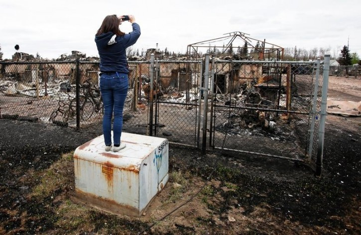 A woman takes photos of the burned remains of a house in the Abasand neighbourhood of Fort McMurray, Alberta, Canada, May 9, 2016 after wildfires forced the evacuation of the town. REUTERS/Chris Wattie
