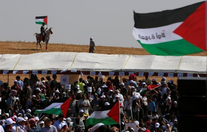 An Arab-Israeli man holds a Palestinian flag during a protest to mark the right of return for refugees who fled their homes during the 1948 ArabÐIsraeli War, at a village near Rahat in southern Israel, May 12, 2016. The 1948 war followed the creation of Israel, which marks its 68th Independence Day this year. REUTERS/Ammar Awad