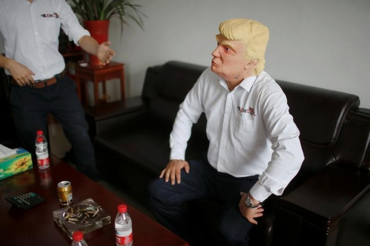 The manager of Jinhua Partytime Latex Art and Crafts Factory wears a mask of U.S. Republican presidential candidate Donald Trump as he poses after talking to reporters in Jinhua, Zhejiang Province, China, May 25, 2016. REUTERS