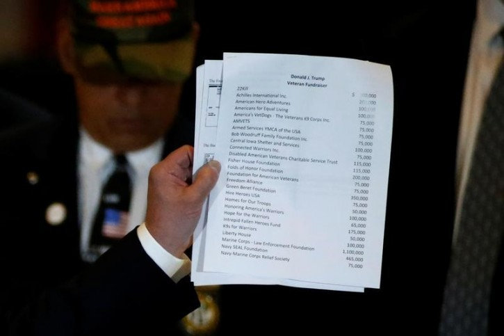 U.S. Republican presidential candidate Donald Trump holds up a list of veterans' groups he says he has donated to, during a press conference at Trump Tower in the Manhattan borough of New York, U.S., May 31, 2016 REUTERS/Carlo Allegri