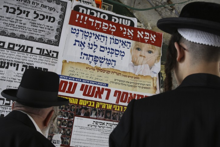 """FILE - Ultra orthodos Jewish men look on a poster reading """"Dad I am scared! The internet and i-phone are endangering our lives"""", posted on a wall in the ultra orthodox Jewish neighborhood of Meah Shearim September 28, 2014. Photo by Nati Shohat/FLASH90"""
