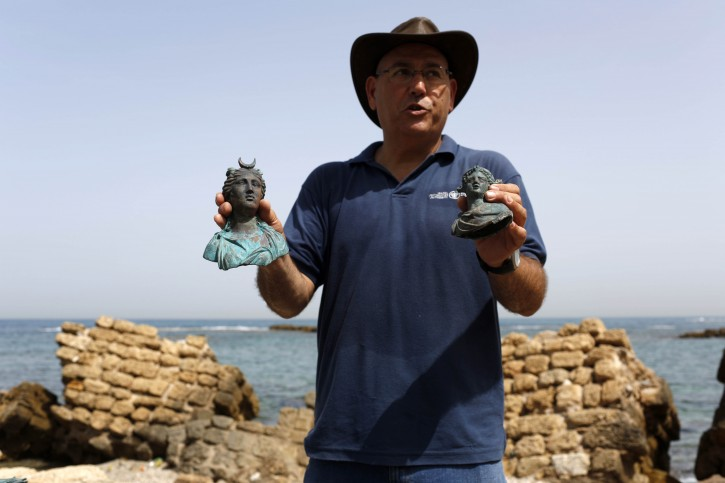 Jacob Sharvit, director of the Marine Archaeology Unit of the Israel Antiquities Authority displays two of the archeological finds at the ancient port of Caesarea, Israel, 16 May 2016. EPA