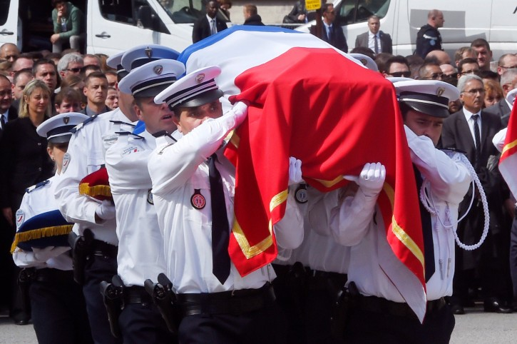 Police officers carry the coffin of one of the two police officials killed by an  extremist claiming allegiance to IS, during a ceremony  Friday, June 17, 2016 in Versailles, near Paris.  Police commander Jean-Baptiste Salvaing and his companion, police administrator Jessica Schneider were stabbed Monday by attacker Larossi Abballa, who was killed in a police raid. (Dominique Faget, Pool via AP)
