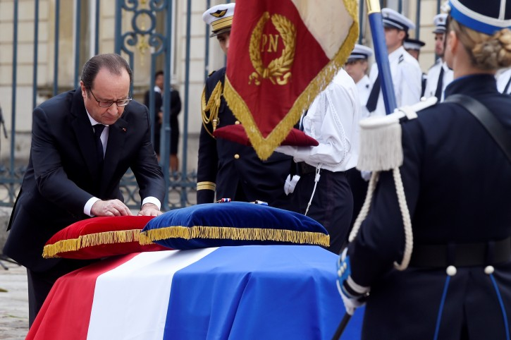 French President Francois Hollande awards posthumously the Legion d'Honneur at one the two police officials killed by an  extremist claiming allegiance to IS,  Friday, June 17, 2016 in Versailles, near Paris.  Police commander Jean-Baptiste Salvaing and his companion, police administrator Jessica Schneider were stabbed Monday by attacker Larossi Abballa, who was killed in a police raid. (Dominique Faget, Pool via AP)