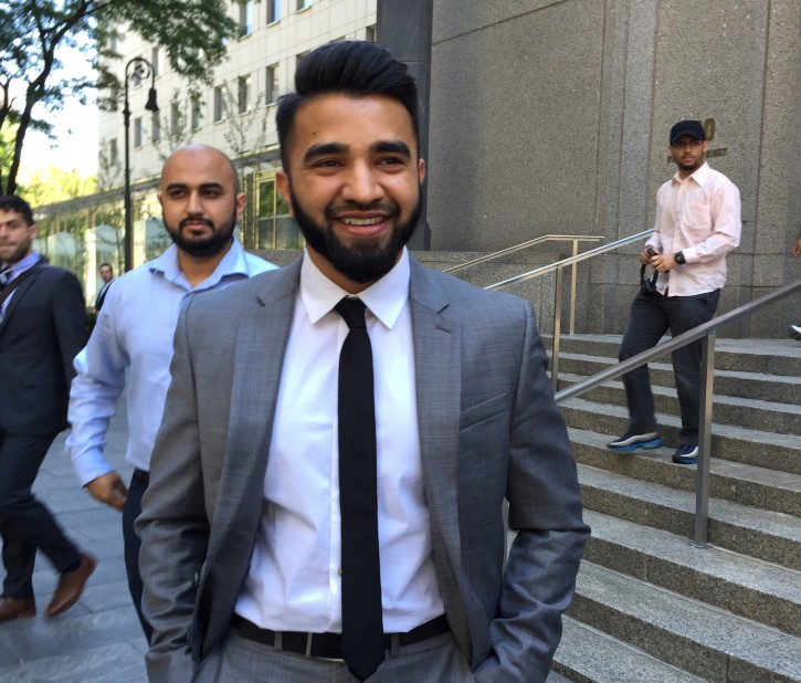 New York Police Department Officer Masood Syed, a practicing Muslim, center, smiles as he leaves Manhattan federal court in New York Wednesday, June 22, 2016, after a judge ordered the city to reinstate his salary and benefits after he sued the city over police rules requiring that anyone exempt from the department's no beard policy for religious or other reasons limit beard length to one millimeter. The NYPD suspended Syed a day earlier without pay. A hearing on the lawsuit is set for July. (AP Photo/Larry Neumeister)