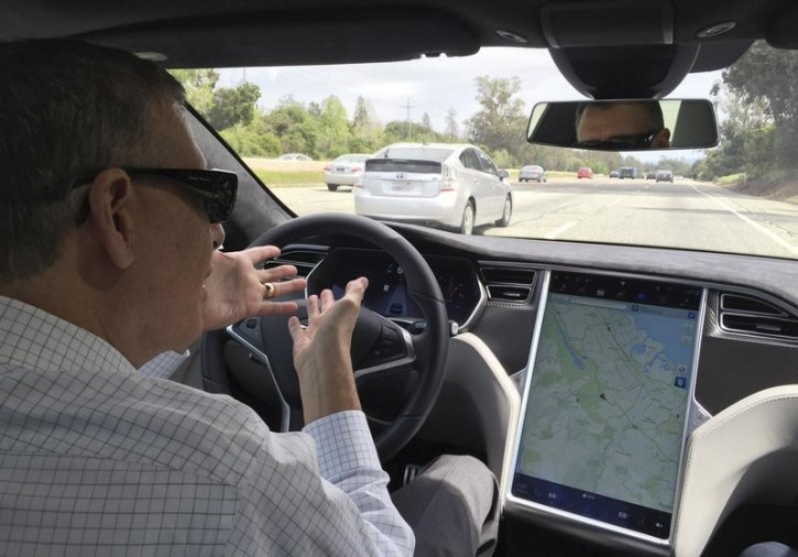 FILE - Reuters journalist Paul Ingrassia sits in the drivers seat of a Tesla S-Type in Autopilot mode in San Francisco, California, U.S., April 7, 2016. REUTERS