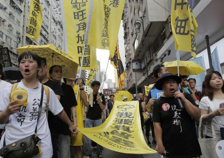 "Protesters carry a banner with Chinese words ""I want genuine universal suffrage""as they march at a down town street during an annual pro-democracy protest in Hong Kong, Friday, July 1, 2016.  AP"