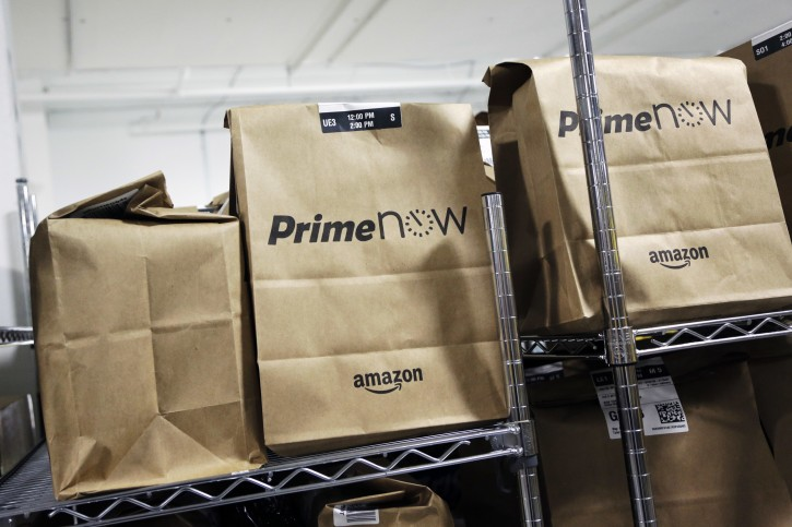 FILE - In this Tuesday, Dec. 22, 2015, file photo, bags are loaded for delivery at Amazon's urban fulfillment facility in New York. The crux of Amazon's $99 annual Prime loyalty program is its free two-day shipping option. (AP Photo/Mark Lennihan, File)
