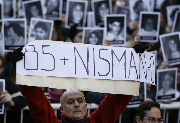 "A man holds a sign that reads in Spanish: ""Eighty-five plus Nisman equals zero"" on the 22nd anniversary of the bombing of the AMIA Jewish center that killed 85 people in Buenos Aires, Argentina, Monday, July 18, 2016. The attack and death of Alberto Nisman, the prosecutor investigating the attack, are still unsolved. (AP Photo/Natacha Pisarenko)"
