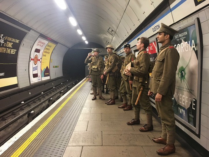 Men dressed as First World War soldiers stand on the platform in Euston underground station in London, to mark 100-years since the start of the Battle of the Somme, early Friday July 1, 2016. London commuters were met by the eerie sight of people dressed as World War I soldiers as they made their way to work Friday, with the soldiers singing wartime songs or remaining silent, revealed later Friday as a tribute, the work of Turner Prize-winning artist Jeremy Deller, National Theatre Director Rufus Norris and thousands of volunteers. (Sarah Perry / PA via AP)