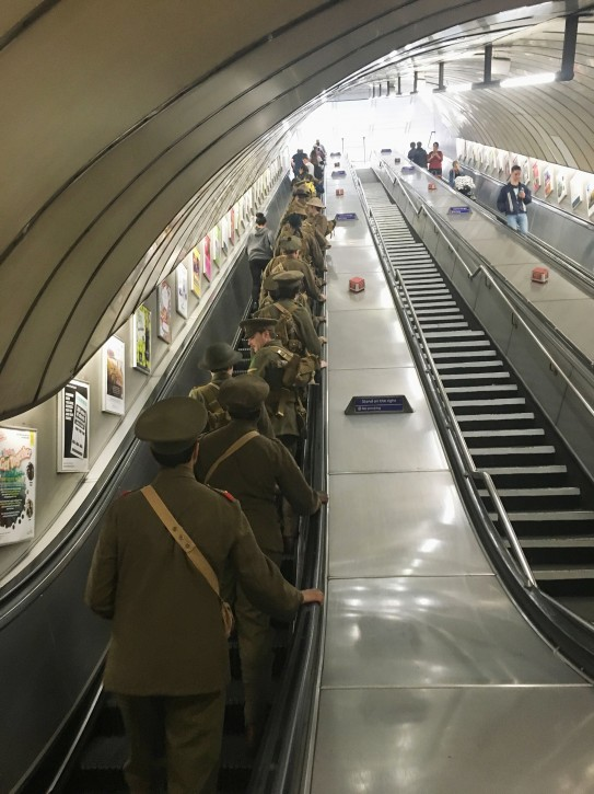 Men dressed as First World War soldiers stand on an escalator as they leave Euston underground station in London, to mark 100-years since the start of the Battle of the Somme, early Friday July 1, 2016. London commuters were met by the eerie sight of people dressed as World War I soldiers as they made their way to work Friday, with the soldiers singing wartime songs or remaining silent, revealed later Friday as a Somme tribute, the work of Turner Prize-winning artist Jeremy Deller, National Theatre Director Rufus Norris and thousands of volunteers. (Sarah Perry / PA via AP)