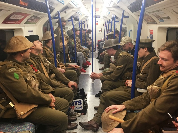 Men dressed as First World War soldiers mingle with regular commuters aboard an underground tube train in London, to mark 100-years since the start of the Battle of the Somme, early Friday July 1, 2016. London commuters were met by the eerie sight of people dressed as World War I soldiers as they made their way to work Friday, with the soldiers singing wartime songs or remaining silent, revealed later Friday as a Somme tribute, the work of Turner Prize-winning artist Jeremy Deller, National Theatre Director Rufus Norris and thousands of volunteers. (Sarah Perry / PA via AP)