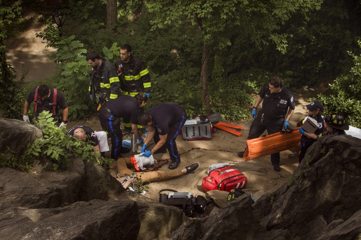 A man, center bottom, bleeds from his injured leg as he gets helped from paramedics, firemen, and police in Central Park in New York, Sunday, July 3, 2016. AP