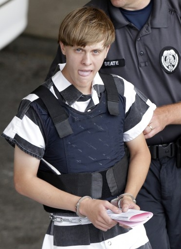 FILE - In this Thursday, June 18, 2015, file photo, Charleston, S.C., shooting suspect Dylann Storm Roof is escorted from the Cleveland County Courthouse in Shelby, N.C.  The families of some of the nine people killed in a South Carolina church are suing the FBI. Their lawsuit accuses the federal government of errors that enabled Dylann Roof to buy the .45-caliber handgun used in the June 2015 shootings at Emanuel AME Church in Charleston. (AP Photo/Chuck Burton, File)