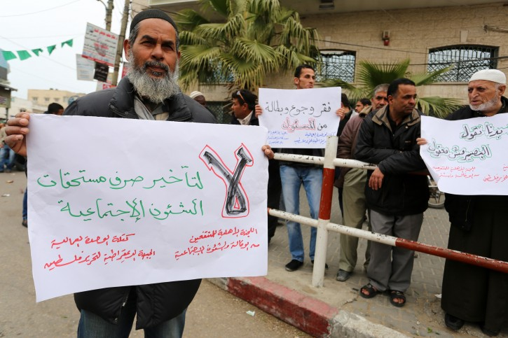 FILE - Palestinians with low income take part in a demonstration calling the Ministry of social affairs to pay their allocations and providing social assistance, in Rafah in the southern Gaza Strip, on February 15, 2015.  Flash90
