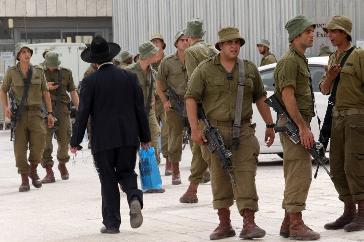 FILE - An Ultra Orthodox man walks past a group of Israeli soldiers. Flash90