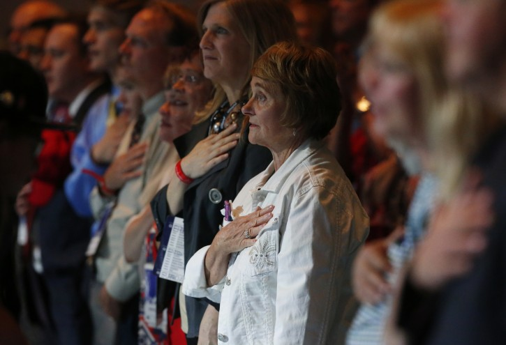 Participants stand for he recitation of the Pledge of Allegiance as they wait for the arrival of Republican presidential candidate Donald Trump to speak during the opening session of the Western Conservative Summit Friday, July 1, 2016, in Denver. The summit, which brings together Republicans from across the West, runs through Sunday. (AP Photo/David Zalubowski)