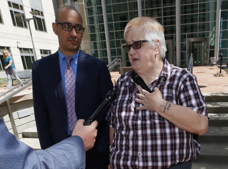 Dana Zzyym, of Fort Collins, Colo., right, talks about the arguments in a hearing on Zzyym's lawsuit requiring people to pick a gender to get a passport outside the U.S. Federal Courthouse early Wednesday, July 20, 2016 in Denver. Zzyym, who was born with ambiguous sex characteristics, claims that requiring people to designate their sex to get a passport is discriminatory. Zzyym's attorney, Paul D. Castillo, from the south-central regional office of Lambda Legal in Dallas, looks on. (AP Photo/David Zalubowski)