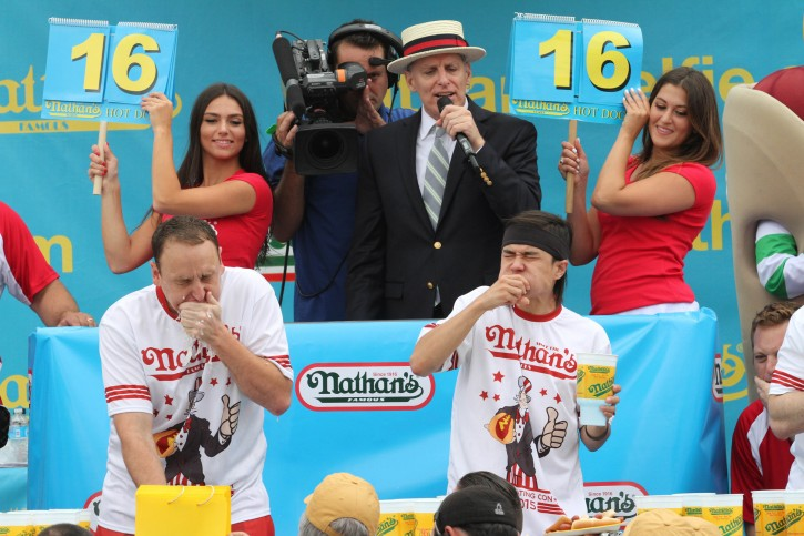 FILE - In this July 4, 2015 file photo, Joey Chestnut, left, and Matt Stonie compete in Nathan's Famous Fourth of July International Hot Dog Eating Contest men's competition Saturday  in the Coney Island section in the Brooklyn borough of New York. Stonie came in first eating 62 hot dogs and buns in 10 minutes. Chestnut came in second eating 60 hot dogs and buns in 10 minutes.For decades, the showmen behind the annual  contest have been teling reporters the tradition began in 1916 with a showdown between patriotic immigrants on the Coney Island boardwalk. That would make this year's contest a centennial, of sorts, except for an inconvenient truth: the backstory was invented  in the 1970s by PR men trying to get the hot dog stand on the map. (AP Photo/Tina Fineberg, File)