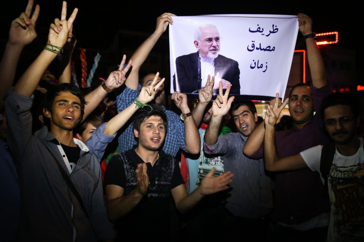 """FILE -- In this July 14, 2015 file photo, young Iranian men cheer and show victory signs while holding a picture of Foreign Minister Mohammad Javad Zarif, reading """"Zarif is Mosaddegh of our time,"""" comparing Zarif to Mohammad Mosaddegh, Iran's legendary prime minister during the 1950s who nationalized the country's oil industry, in Tehran, Iran. AP"""